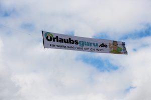 Bannerfliegen – Luftwerbung von Urlaubsguro auf einem Werbebanner von Profi Events